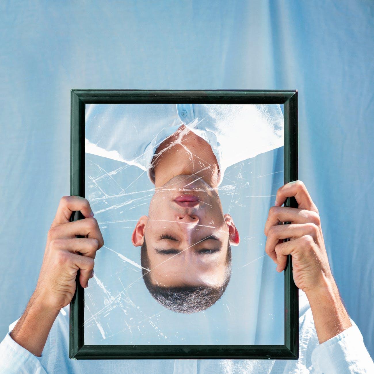 man closing his eyes reflection on mirror